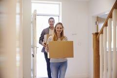 Bärande askar för par in i nytt hem på rörande dag Arkivbild