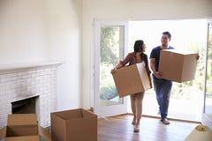 Bärande askar för par in i nytt hem på rörande dag Royaltyfri Fotografi