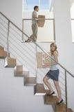 Bärande askar för par uppför trappan i nytt hem arkivfoto