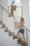 Bärande askar för par uppför trappan i nytt hem Royaltyfri Foto