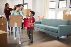 Bärande askar för upphetsad familj in i nytt hem på rörande dag fotografering för bildbyråer