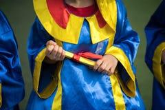 Bärande avläggande av examenklänning för förskole- unge och innehavdiplomcloseup royaltyfri fotografi