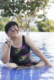 Bärande baddräkt för knubbig kvinna och bärande solexponeringsglas med Arkivfoton