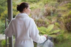 Bärande badrock för kvinna mot suddiga växter Royaltyfri Foto