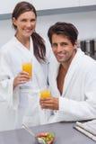 Bärande badrockar för älskvärda par och innehavexponeringsglas av orange juic Arkivbild