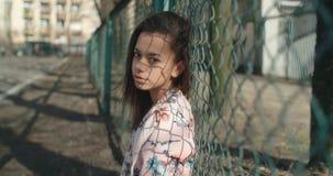Bärande bombarjacka för ung härlig kvinna som poserar över metallstaketet Arkivbild