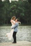 Bärande brud för brudgum nära sjön och skog royaltyfri fotografi