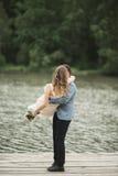 Bärande brud för brudgum nära sjön och skog royaltyfri bild