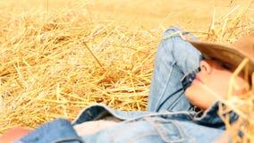 Bärande cowboyhatt för fridsam kvinna som ligger i hö stock video