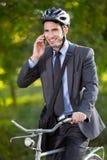 Bärande cykelhjälm för ung affärsman och användamobiltelefon arkivfoto