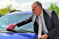 Bärande dräkt för man som gör ren en bil. Royaltyfri Bild