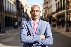 Bärande dräkt för stilig svart man i stads- bakgrund Arkivbild