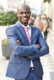 Bärande dräkt för stilig svart man i stads- bakgrund royaltyfria bilder