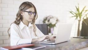 Bärande exponeringsglas för en ung härlig kvinna som i regeringsställning skriver på hennes bärbar dator Skjutit medel arkivbild