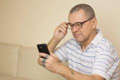 Bärande exponeringsglas för gamal man som delvis använder hans smartphone med ögon c arkivfoto