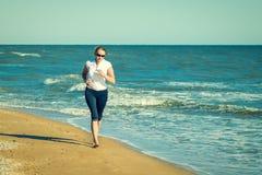 Bärande exponeringsglas för kvinna med kal fot som joggar på stranden royaltyfri bild