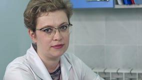 Bärande exponeringsglas för kvinnlig doktor som sitter på hennes skrivbord som ser direkt på kameran stock video