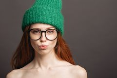 Bärande exponeringsglas för ljust rödbrun kvinna och grön hatt som trutar hennes kanter som är klara för kyss Royaltyfri Bild