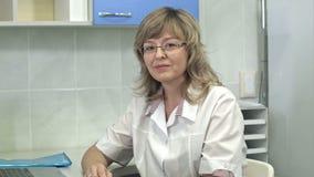Bärande exponeringsglas för säker kvinnadoktor som ser kameran med ett allvarligt uttryck lager videofilmer
