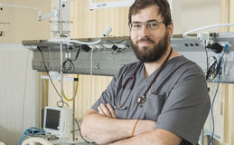 Bärande exponeringsglas för skäggig doktor och gråa arbeten för en ämbetsdräkt med sjukhusutrustning fotografering för bildbyråer