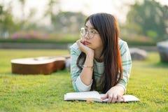 Bärande exponeringsglas för tonårs- flicka som ner ligger med gitarren och böcker på fältet på solnedgången arkivfoton