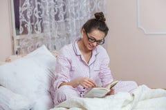 Bärande exponeringsglas för ung kvinna medan läsebok i säng Avkopplad kvinna som ligger i säng i sleepwear som läser en bok Arkivbild
