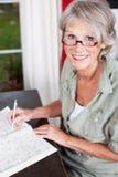 Bärande exponeringsglasarbete för äldre kvinna Arkivfoton