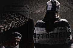Bärande fängelselikformig för kvinnlig fånge med den sydde nummerstandinen Royaltyfri Fotografi