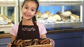 Bärande förkläde för förtjusande liten flicka som arbetar på bagerit som ler till kameran arkivfoton