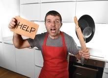 Bärande förkläde för rolig förskräckt maninnehavpanna på kök som frågar för hjälp Arkivbilder