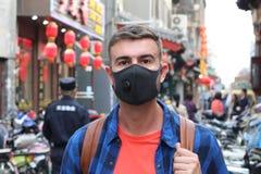 Bärande föroreningmaskering för Caucasian man i Asien arkivfoton
