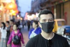 Bärande föroreningmaskering för man utomhus royaltyfria foton