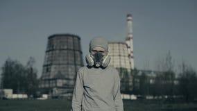 Bärande föroreningmaskering för ung pojke mot fabrikslampglas Luftf?roreningbegrepp Unge i grå kopp och respirator arkivfilmer