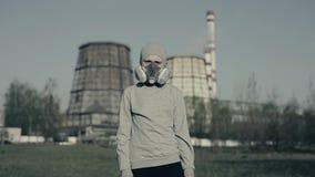 Bärande föroreningmaskering för ung pojke mot fabrikslampglas Luftf?roreningbegrepp Unge i grå kopp och respirator lager videofilmer