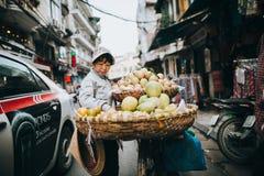 bärande frukter för kvinna på cykeln på den upptagna gatan i Hanoi, Vietnam Royaltyfri Bild