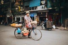 bärande frukter för man på cykeln på vägen i Hanoi, Vietnam Royaltyfri Foto