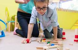 Bärande glasögon för förträningspojke, medan spela med träleksaker royaltyfria bilder
