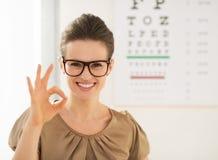 Bärande glasögon för kvinna som ok visar gest nära det Snellen diagrammet Arkivbild