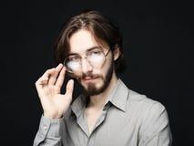 Bärande glasögon för ung man över svart bakgrund royaltyfri bild