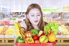 Bärande grönsaker för ung kvinna i livsmedelsbutik Royaltyfria Bilder