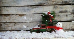 Bärande gran för leksakbil med snögubben arkivfilmer