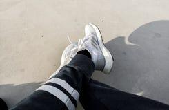 Bärande gymnastikskor, ADIDAS ÖKAR ULTRA, vita och gråa skor arkivfoto
