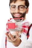 Bärande hängslen för man med den lilla shoppingkorgen royaltyfria foton