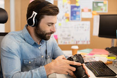 Bärande hörlurar för fotograf, medan genom att använda kameran i idérikt kontor Royaltyfria Bilder