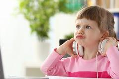 Bärande hörlurar för liten flicka genom att använda aggressivt artikulera för dator arkivfoto