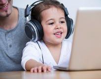 Bärande hörlurar för liten flicka, medan se bärbara datorn med fadern på tabellen i hus Arkivbild