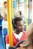 Bärande hörlurar för man som lyssnar till musik på bussresa royaltyfria foton