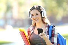 Bärande hörlurar för student som ser dig royaltyfri bild