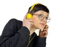 Bärande hörlurar för ung kvinna som lyssnar till musik royaltyfri foto