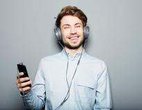 Bärande hörlurar för ung man och innehavmobiltelefon arkivfoton